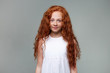Portrait of cute little girl with ginger hair and freckles, smiles and calming looks at the camera, stands over gray background.