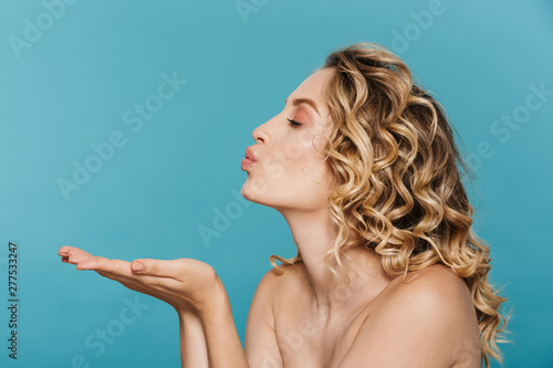 Obraz Image in profile of young shirtless woman 20s with curly blond hair blowing air kiss at copyspace - fototapety do salonu