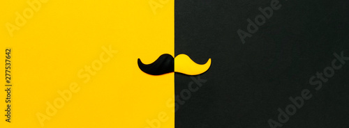 Fototapeta Creative party decoration concept. Black and yellow mustache, props for photo booths, carnival parties on black yellow background top view flat lay copy space Father's day Men's health awareness month obraz na płótnie