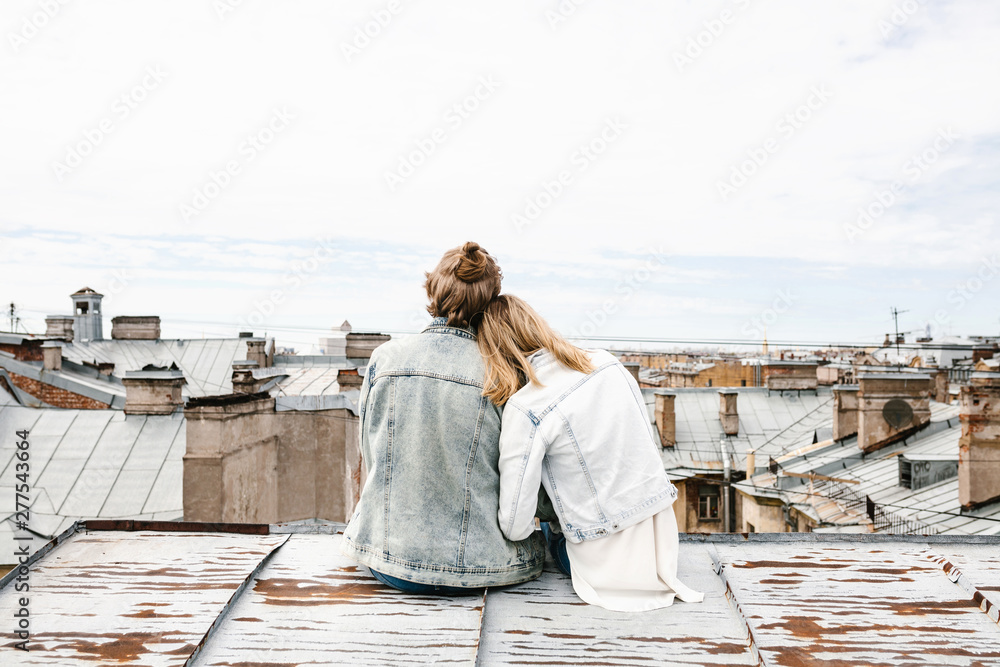 Fototapety, obrazy: A young couple sits on the roof and admires a beautiful view of the city. Romance, love and trusting relationships. Or he dream or digital detox together.