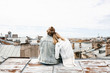Leinwandbild Motiv A young couple sits on the roof and admires a beautiful view of the city. Romance, love and trusting relationships. Or he dream or digital detox together.