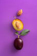 canvas print picture - Plum. Whole and half fruit on a purple background viewed from above. Top view