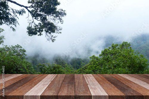 Foto auf Gartenposter Cappuccino Wood old table against landscape mountain and fog background. For your product placement or montage with focus to the table top in the foreground