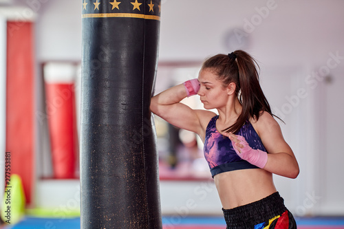 Muay thai girl practicing with heavy bag Canvas Print