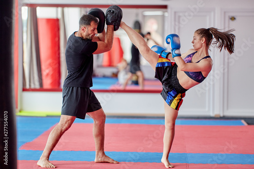 Woman training kickboxing with coach Wallpaper Mural