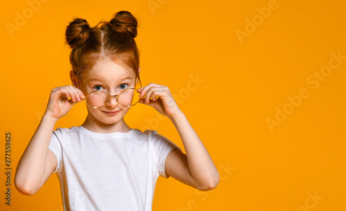 Beautiful young girl with red hair with a bagel in her stylish glasses looks at you in the frame Wallpaper Mural
