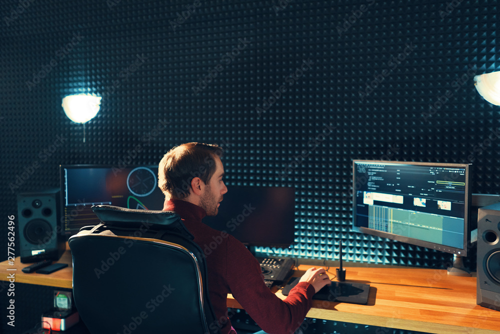 Fototapety, obrazy: Back view of young man watching graphs on monitors