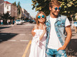 Smiling beautiful girl and her handsome boyfriend. Woman in casual summer dress and man in jeans clothes. Happy cheerful family. Female having fun on the street background.Hugging couple in sunglasses