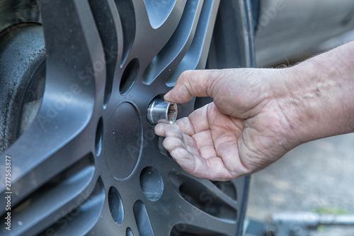 Fényképezés Closeup of a hand attaching a screw to the wheel of a car.