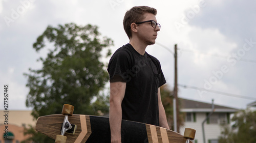 Fotografering  A young man wearing a black shirt and glasses looking straight ahead from a side angle holds his wooden longboard really to ride through the towns neighborhoods on a bright and beautiful  cloudy day
