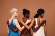 canvas print picture - Three diverse women standing against brown background hugging each other