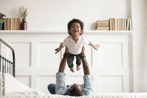 Obraz Happy african kid boy flying in fathers arms on bed - fototapety do salonu