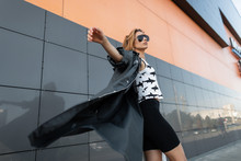 Modern Pretty Young Hipster Woman In Trendy Dark Sunglasses In A Stylish Long Jacket In A Black T-shirt With A Pattern In Black Shorts Travels The Streets Of The City.Beautiful European Girl On A Walk