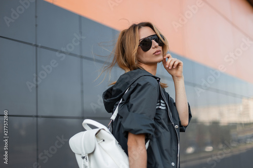 Modern pretty young hipster woman in a trendy gray jacket with a white stylish leather backpack in sunglasses on the street near a gray modern building on summer day Fototapete
