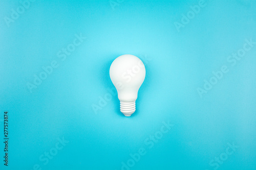 Photographie  white light bulb is shine on blue table