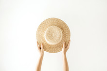 Minimalistic Summer And Travel Concept. Woman's Hands Holding A Straw Yellow Hat. Front View.