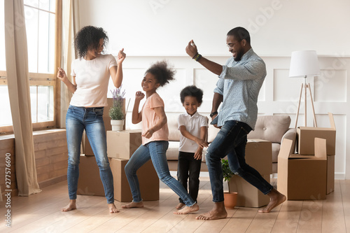 Fotografía  Happy african american parents and children dancing celebrating moving day