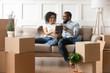 Leinwandbild Motiv Smiling black couple use digital tablet on moving day