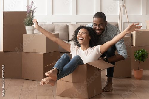 Fotografiet  Happy african young couple riding in box on moving day