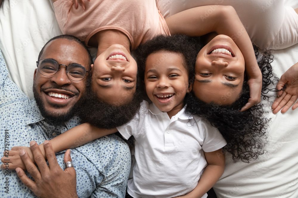 Fototapety, obrazy: Happy african family lying on bed cuddling, portrait, top view