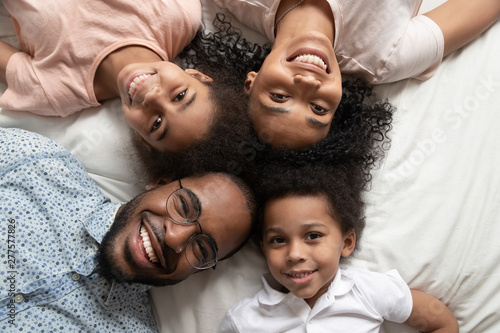 Obraz Happy african family looking at camera on bed, top view - fototapety do salonu