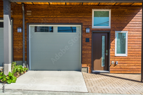 Fényképezés  Entrance and garage doors of brand new townhouse with wooden siding wall siding