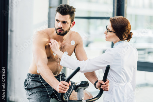 фотографія  doctor conducting endurance test and putting electrodes on sportsman