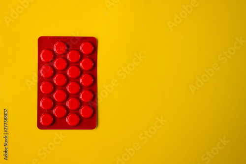 red pack pills on yellow background with copy space Canvas Print
