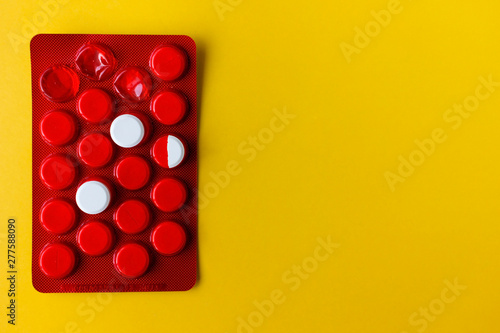 two white round pills and half are on the red packaging with copy space Wallpaper Mural
