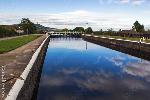 Poster Channel Caledonian Canal Locks in Inverness in Scotland. It is a 60miles long canal in Scotland that starts in Inverness and ends in Fort William connecting the east coast with the west coast.