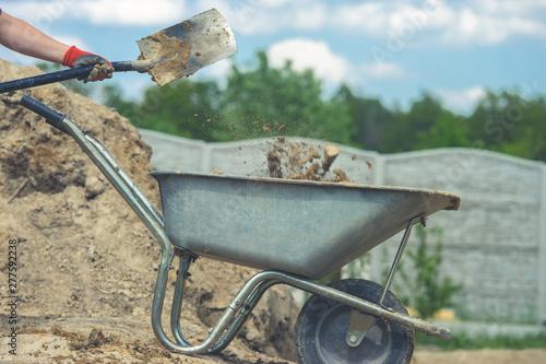 Tela Digging with a shovel. Throwing the soil into a wheelbarrow