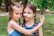 Two Cute Little Girls Having Fun In Park In Sunny Summer Day