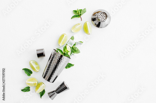 Poster de jardin Bar Set of bar accessories for cocktail making. Shaker, jigger, glass, spoon and other bar tools with lime and mint leaves on withe background.