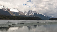 Cloudy Rocky Mountains In British Columbia Reflecting In The Icy Water