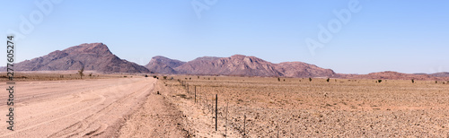Photo Gravel dirt road leading towards mountains in Central Namibia