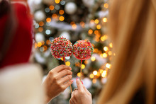 2 Women Holding 2 Apple In Caramel With Candies In Front Of Christmas Tree And Lights, Focus On Apples