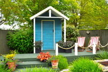 Wooden Blue Painted Garden Tools Storage Shed Among Green Grass, Potted Plants And Pink Deckchairs In Summer In The English Countryside. Northamptonshire, UK