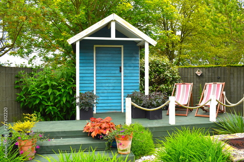Obraz na płótnie Wooden blue painted garden tools storage shed among green grass, potted plants and pink deckchairs in summer in the English countryside