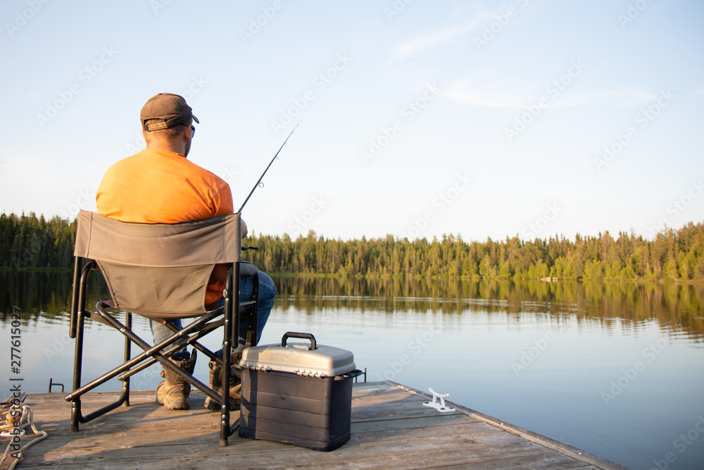 Fototapeta A man fishing on a lake on a wooden dock in Ontario Canada