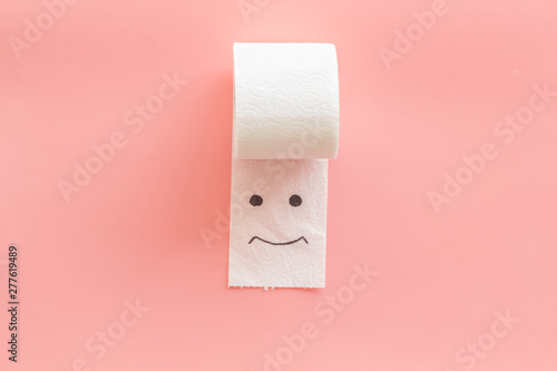 Toilet paper roll with painted face for proctology diseases concept on pink back Canvas Print