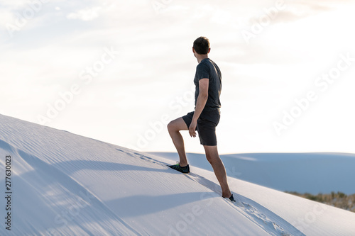 Photo Man climbing walking on sand hill in white sands dunes national monument in New