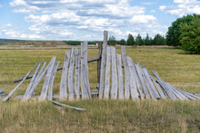 Old Wooden Rickety Fence. Abandoned Field With An Old Wooden Fence. Old Broken Wooden Fence. Summer Sunny Day With Blue Sky And White Clouds. The Effects Of The Hurricane. Disaster
