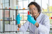The Portrait Of The Asian Smart Man Scientist Is Holding Two Test Tubes. In Research Laboratory
