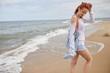 Woman walking on beach. Woman having leisure time walking barefoot on beach during warm autumnal weather