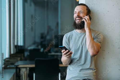 Deurstickers Snelle auto s Business communication. Portrait of bearded hipster guy using two smartphones to talk and chat, laughing. Blur workspace.