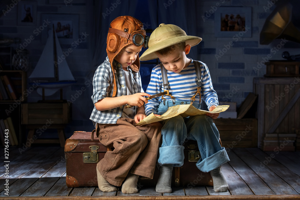 Fototapety, obrazy: Boys imagine themselves as an airplane pilot and a tourist, read the map at night in the moonlight