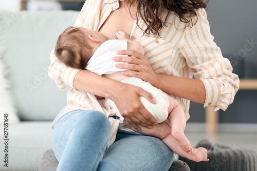 Young woman breastfeeding her baby at home Canvas Print