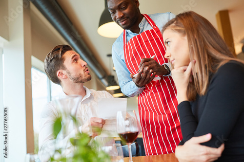 Valokuva  Young couple orders food from a waiter