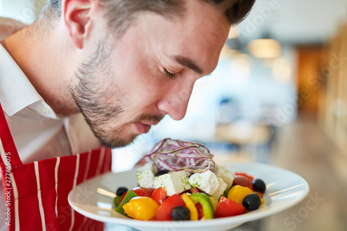 Valokuva  Waiter serving fresh greek salad