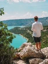 A Blond Man In A White Shirt Stands Over The Verdon Gorge, Turquoise Water, France